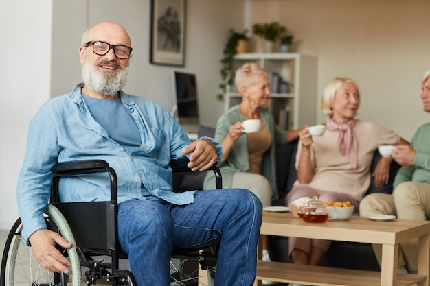 Senior discapacitado barbudo sentado en silla de ruedas y sonriendo a la cámara en el hogar de ancianos