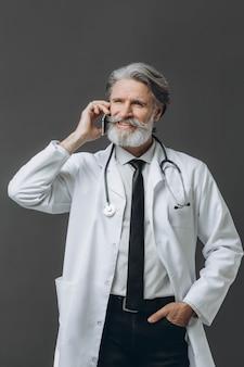 Senior doctor hablando por teléfono móvil