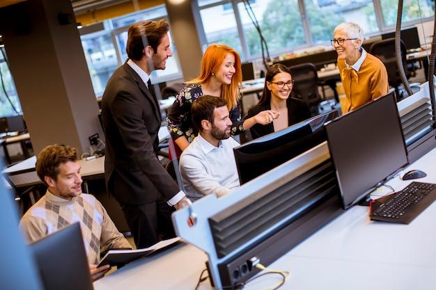 Senior empresaria y jóvenes empresarios trabajan en una oficina moderna