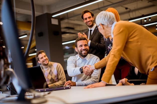 Senior empresaria trabajando junto con jóvenes empresarios en la oficina moderna