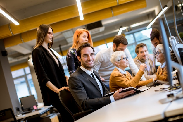 Senior empresaria trabajando junto con jóvenes empresarios en la oficina