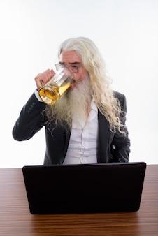 Senior empresario barbudo bebiendo un vaso de cerveza mientras usa el portátil