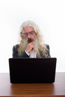 Senior empresario barbudo con portátil sobre mesa de madera