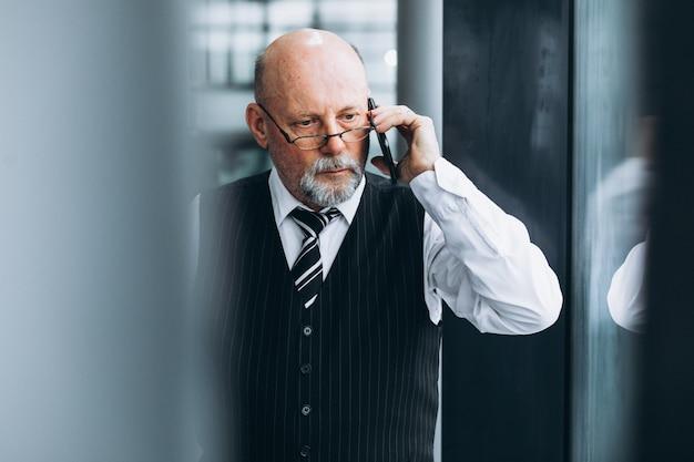Senior empresario hablando por teléfono en la oficina