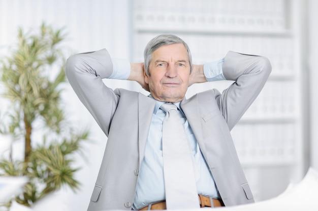 Senior empresario soñando con sentarse en su escritorio en la oficina.