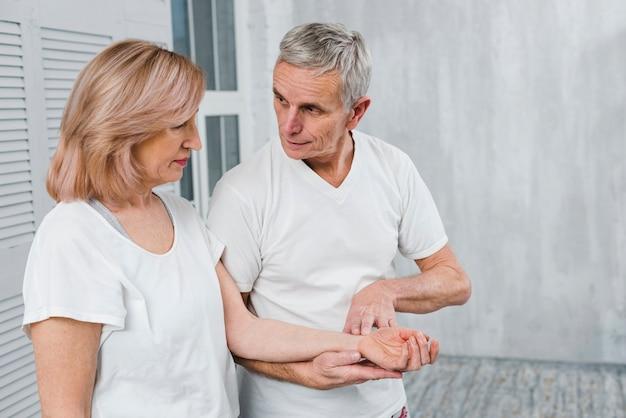 Senior esposo revisando el pulso de su esposa