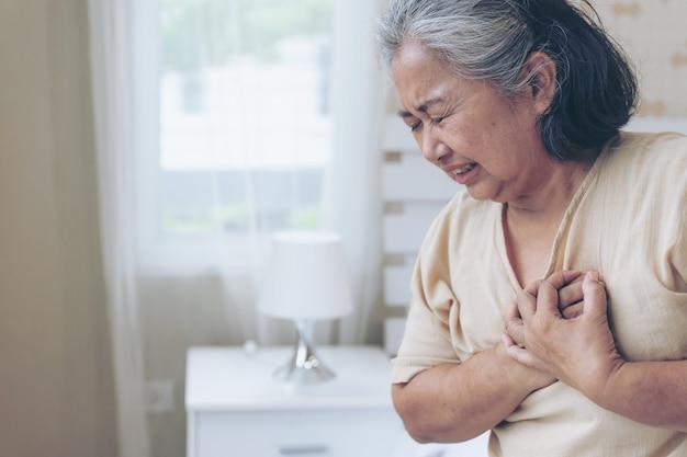 Senior femenino asiático que sufre de un fuerte dolor en el pecho ataque al corazón en casa - enfermedad cardíaca mayor