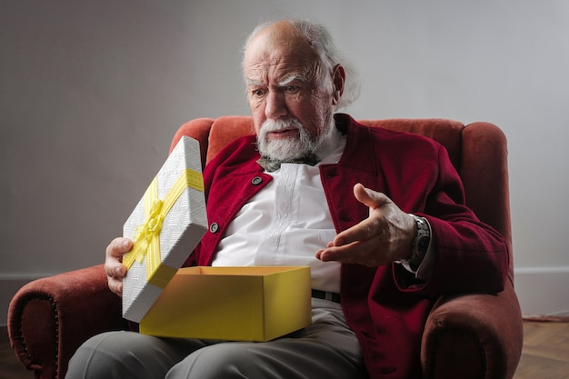 Senior hombre abriendo una caja de regalo