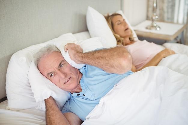 Senior hombre acostado en la cama y tapándose los oídos con la almohada
