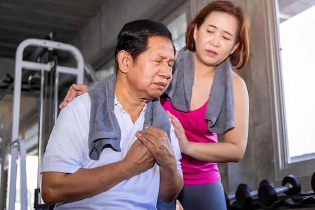Senior hombre asiático ataque al corazón durante el entrenamiento con la esposa en el gimnasio.