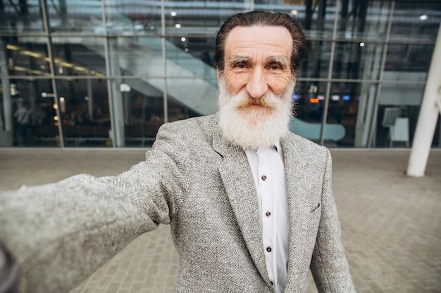 Senior hombre de barba gris con maleta amarilla y mapa de la ciudad hacen selfie en el fondo del edificio del aeropuerto.
