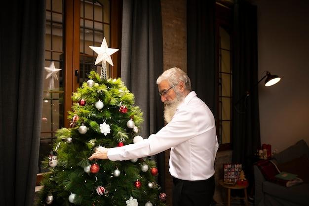 Senior hombre con barba junto al árbol de navidad