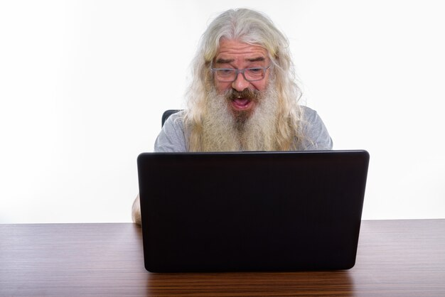Senior hombre barbudo con anteojos mientras usa el portátil