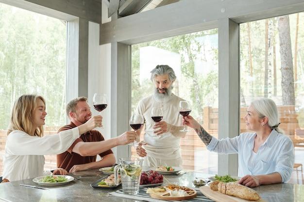 Senior hombre barbudo con copa de vino tinto bebiendo tostadas con miembros de la familia durante la cena