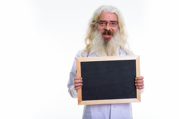 Senior hombre barbudo doctor sosteniendo pizarra en blanco