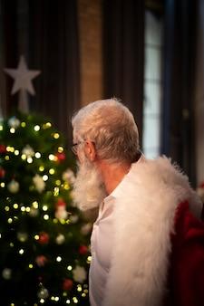 Senior hombre barbudo mirando el árbol de navidad