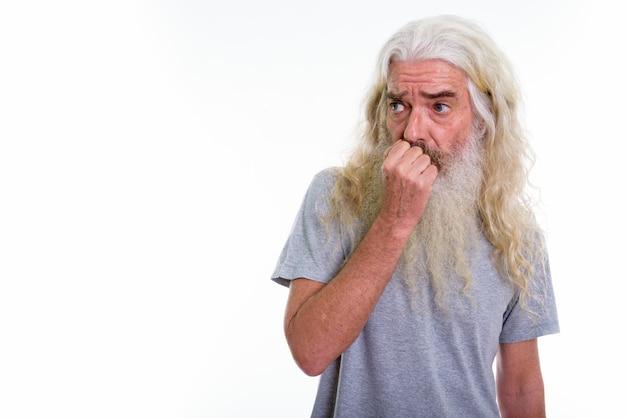 Senior hombre barbudo mirando asustado a un lado
