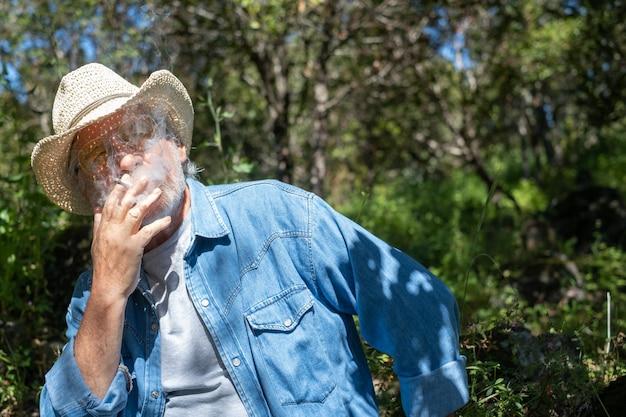 Senior hombre barbudo parcialmente oculto por el humo de su cigarrillo, sentado al aire libre en un bosque verde relajándose y disfrutando de un día soleado