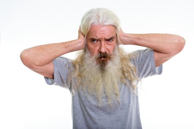 Senior hombre barbudo pensando mientras cubre las orejas
