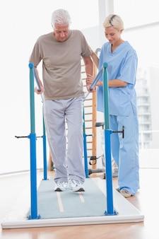 Senior hombre caminando con ayuda del terapeuta