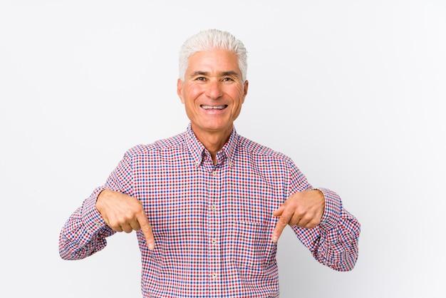 Senior hombre caucásico aislado apunta hacia abajo con los dedos, sentimiento positivo.