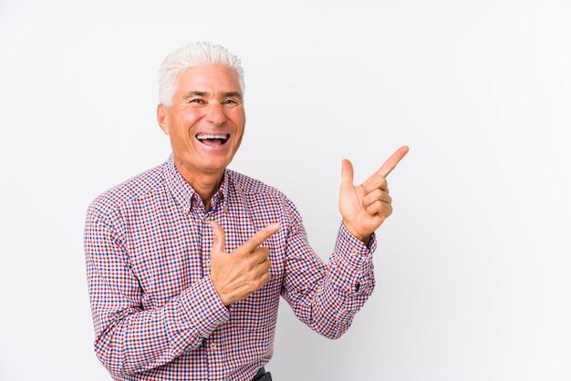Senior hombre caucásico aislado apuntando con los dedos a un espacio de copia, expresando emoción y deseo.