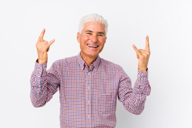 Senior hombre caucásico aislado mostrando gesto de rock con los dedos