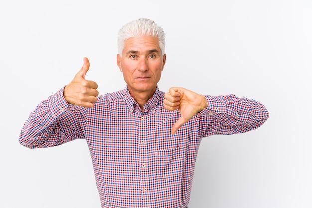 Senior hombre caucásico aislado mostrando los pulgares hacia arriba y hacia abajo, difícil elegir el concepto