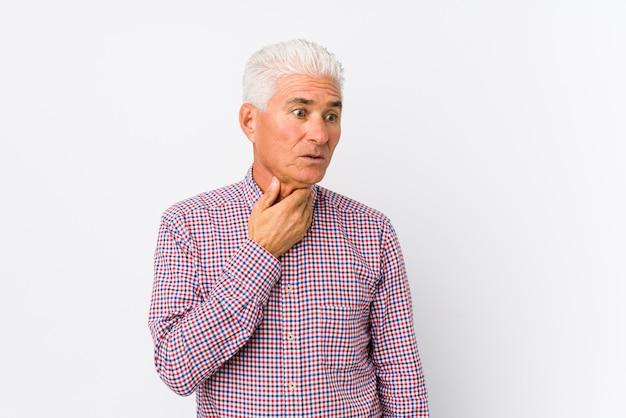 Senior hombre caucásico aislado sufre dolor en la garganta debido a un virus o infección.