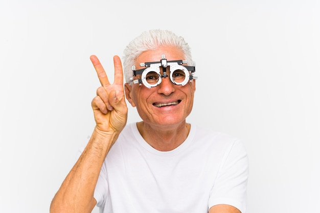 Senior hombre caucásico que llevaba un marco de prueba optometrista mostrando el signo de la victoria y sonriendo ampliamente.