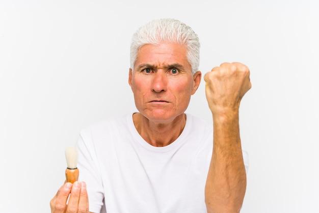 Senior hombre caucásico recientemente afeitado mostrando el puño con agresiva expresión facial.