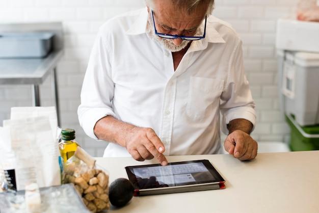 Senior hombre caucásico usando tableta digital