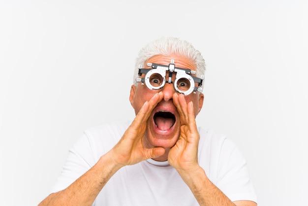 Senior hombre caucásico vistiendo un marco de prueba optometrista gritando emocionado al frente.