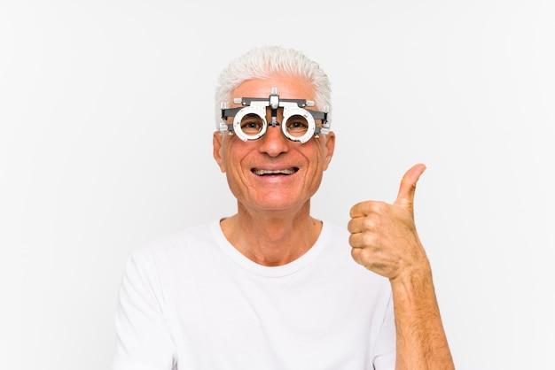 Senior hombre caucásico vistiendo un marco de prueba optometrista sonriendo y levantando el pulgar hacia arriba