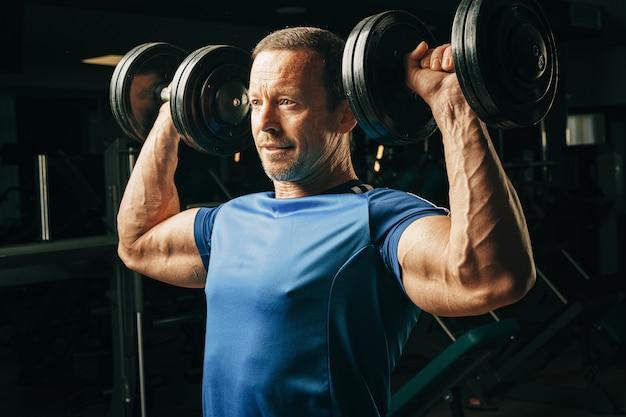 Senior hombre de unos cincuenta años levantando pesas en un gimnasio