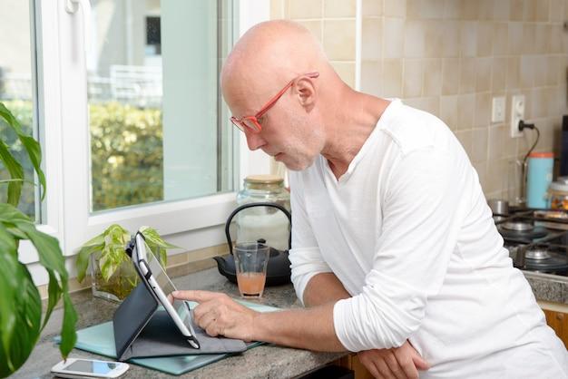 Senior hombre en cocina usando tableta