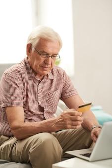Senior hombre de compras en línea en casa