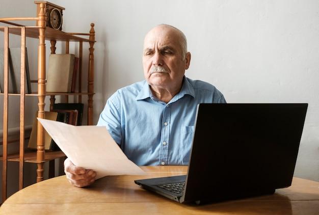 Senior hombre comprobando un documento portátil