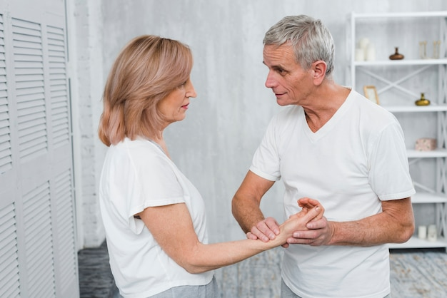 Senior hombre está comprobando el pulso de la mujer