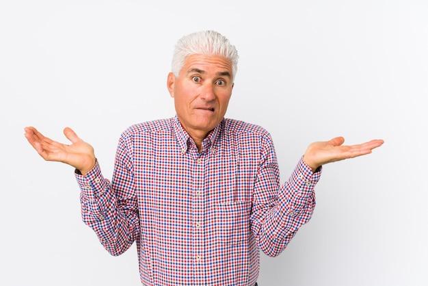 Senior hombre confundido y dudoso encogiéndose de hombros para sostener algo