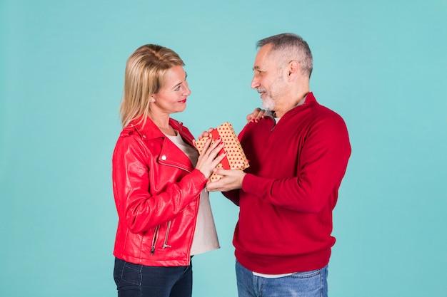 Senior hombre dando presente a su esposa de pie contra el fondo azul