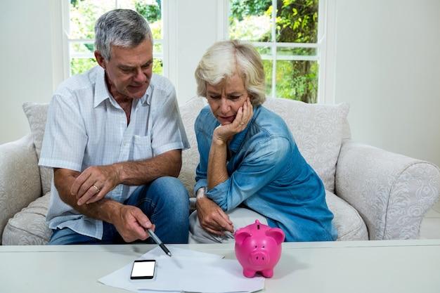 Senior hombre discutiendo con su esposa con respecto a los ahorros en el sofá