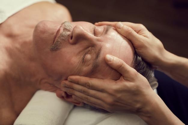 Senior hombre disfrutando de masaje facial en spa