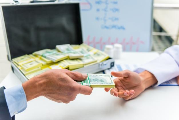 Senior hombre empresario da dinero para el hospital.