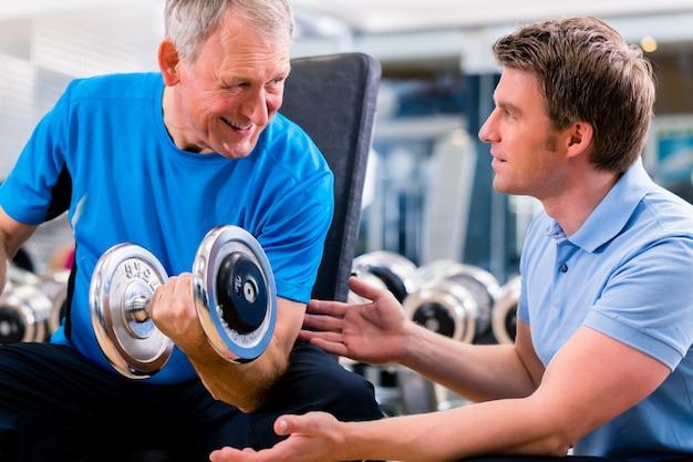 Senior hombre y entrenador en el ejercicio en el gimnasio