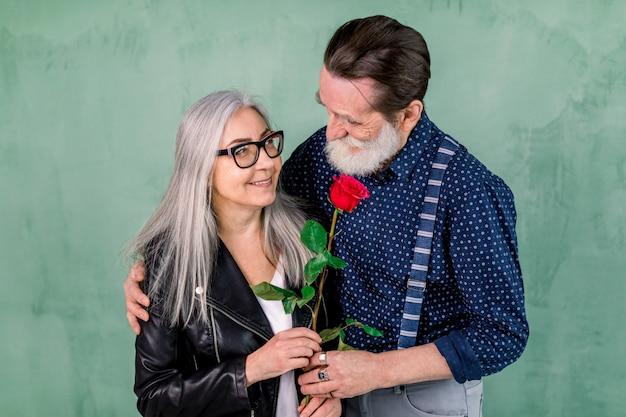 Senior hombre guapo con barba que ofrece una rosa a su compañero, encantadora dama de cabello gris, parados juntos frente a la pared verde