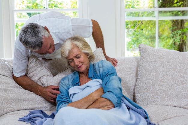 Senior hombre hablando con esposa enferma descansando en el sofá