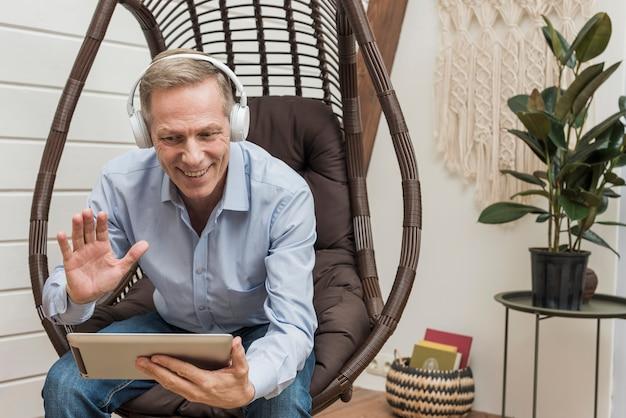Senior hombre hablando con sus hijos a través de una tableta