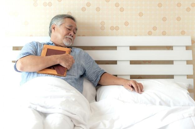 Senior hombre infeliz está llorando, abrazando la imagen de la esposa fallecida