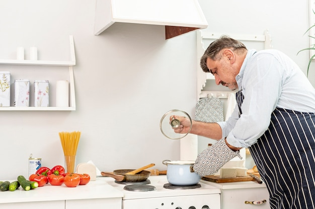 Senior hombre levantando una olla tapa